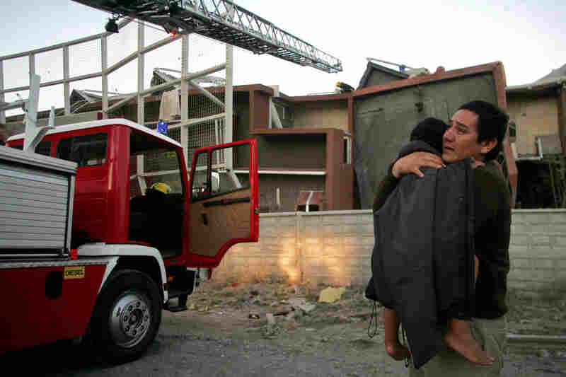 A man holds a child outside a quake-damaged building in Concepcion early on Saturday.