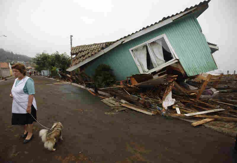 Following one of the largest earthquakes ever recorded, a woman stands in front of a destroyed home in Pelluhue.