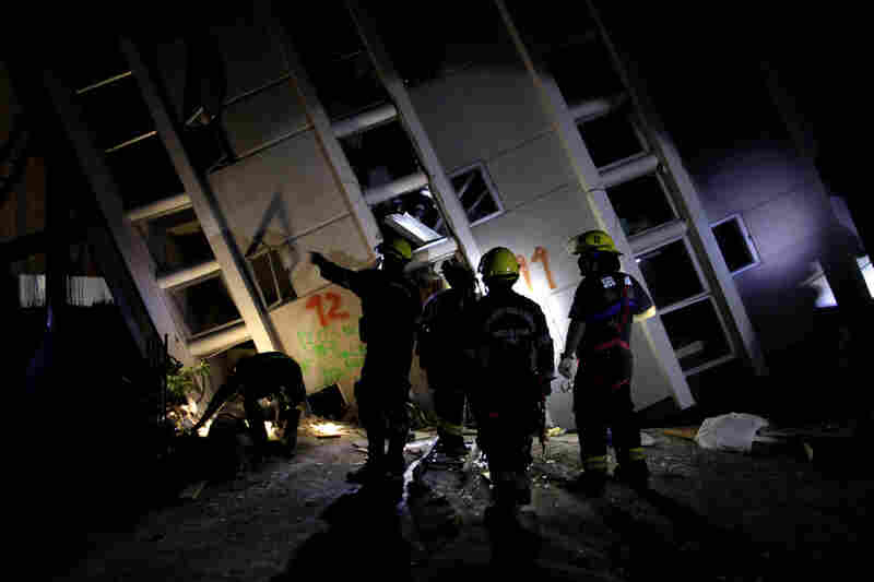 Firemen search for survivors in a destroyed building in Concepcion on Sunday.