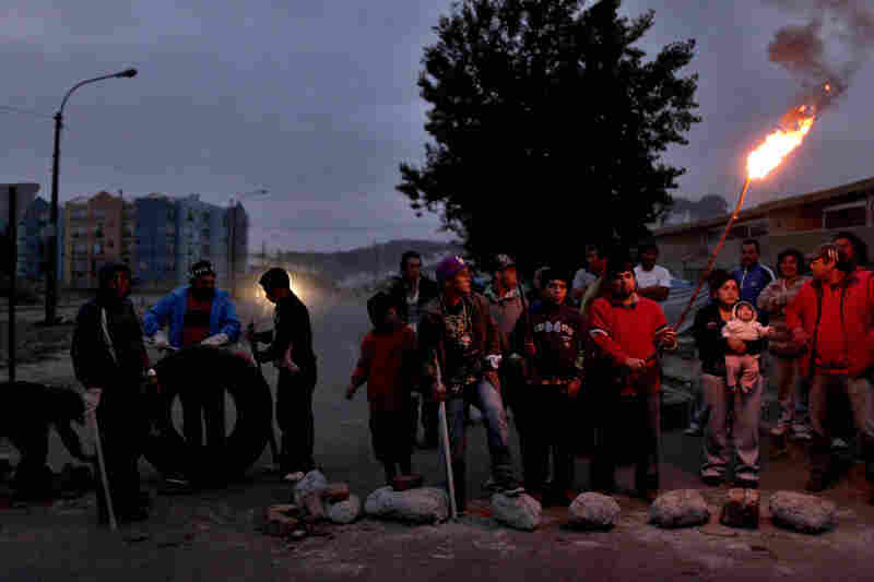 People in Concepcion stand outside guarding their homes on Monday.