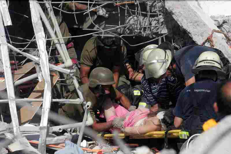 Rescue workers help an injured woman in Concepcion.
