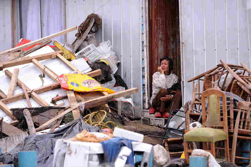 Bejamira Neira Zapata sits in the doorway of her house Monday after the massive earthquake struck the village of Penco. The tsunami engulfed the normally placid Penco and neighboring villages.