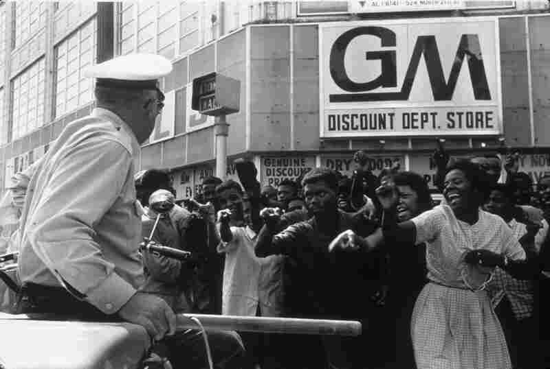 African-American protesters taunt a white police officer during a civil rights demonstration. Birmingham, Ala., 1963