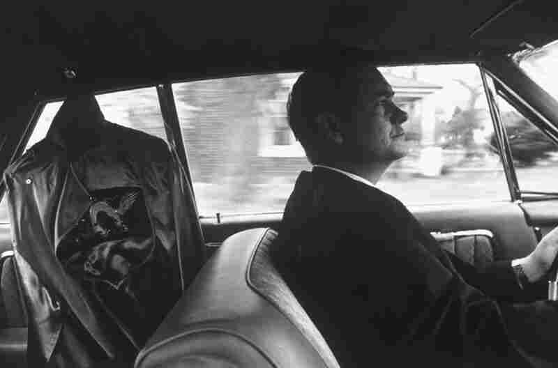 James R. Jones, grand dragon of the Ku Klux Klan, drives to a rally with his Klan robe hanging in the back seat of his car. North Carolina, circa 1964