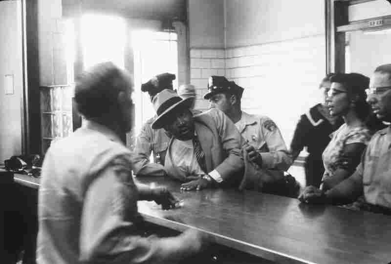 Dr. Martin Luther King Jr.  is sprawled across a police desk as his wife looks on. He was arrested while trying to attend a hearing for civil rights leader Ralph Abernathy and was released when his identity became known to the police. Montgomery, Ala., 1958