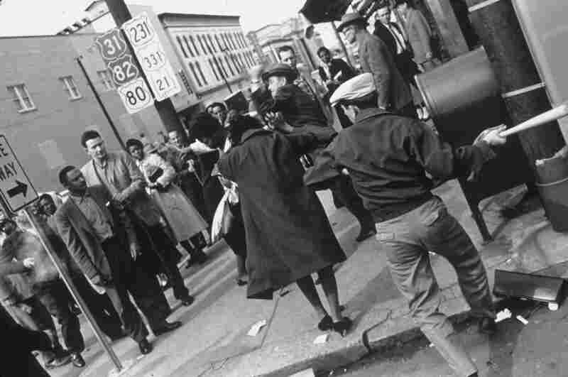 A white man swings a baseball bat at a shopper, while another strikes a black woman in the background. The 1960 attack occurred the day after black students were refused service in the whites-only cafeteria at the state capitol. Montgomery, Ala., 1960