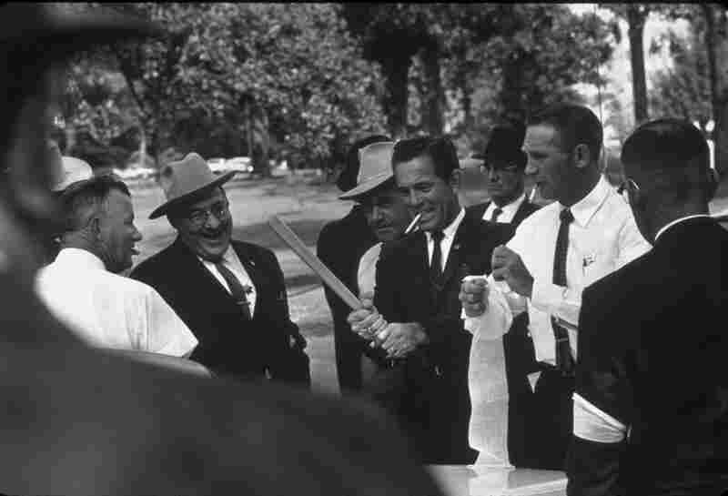 A law officer (center) takes a practice swing with a billy club. The policemen, identified by white armbands, had organized a show of force to back up Lt. Gov. Paul Johnson when he turned James Meredith away from the University of Mississippi. Oxford, Miss., 1962
