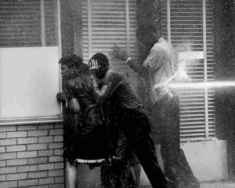 Demonstrators huddled in a doorway seek shelter from the hoses. The water was propelled at a force of  100 pounds per square inch. Birmingham, Ala., 1963