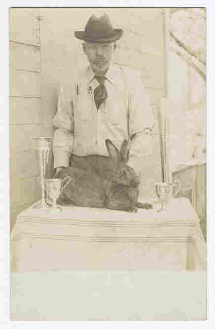 Man with trophies and prize-winning rabbit