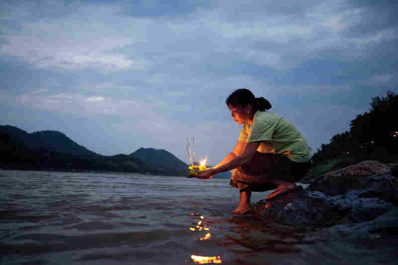 """A woman launches an offering on the Mekong River, known to Laotians as the ""mother of waters,"" during Boun Pi Mai Lao, the New Year's celebration in April."""