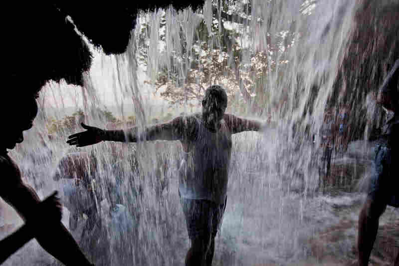 """""""A pilgrim embraces the renewal granted by Saut d'Eau falls at the festival of the Virgin of Miracles in Ville Bonheur, Haiti."""""""