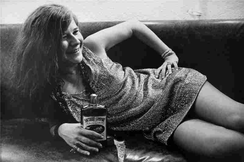 """Janis Joplin holds a bottle of Southern Comfort backstage at San Francisco's Winterland in 1968. """"Janis was a great subject to photograph,"""" Marshall wrote, """"because she was not afraid of the camera and came alive onstage — that was her world."""""""