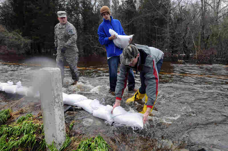 Massachusetts National Guardsmen and local residents place sand bags along Narrows Road in Freetown, Massachusetts on Wednesday. Heavy rains over the last few days have caused widespread flooding in New England, closing schools and government offices.