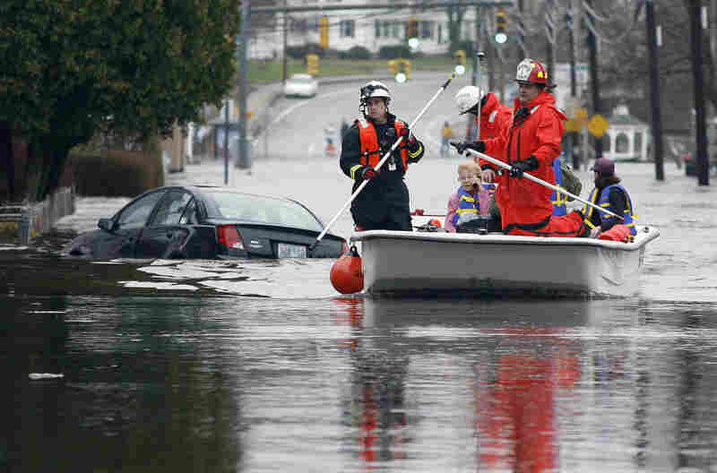 In West Warwick, R.I., firefighters evacuate residents from their flooded houses near the Pawtuxet River on Tuesday.