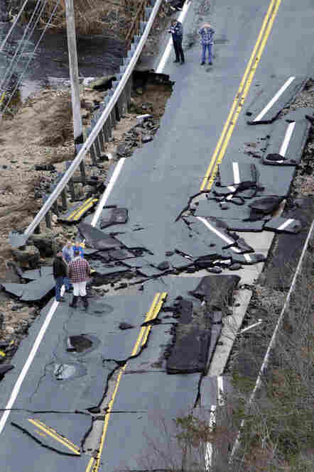 People examine a road washed out along the Wood River in Hopkinton, R.I. on Wednesday. Rhode Island rivers overflowed, causing flooding and road closures after three days of record-breaking rains.