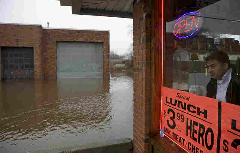 Mohammad Afzaal, owner of One Stop Deli, looks out at the flooded section along Jericho Turnpike that has killed 90 percent of his day's business in Huntington, N.Y., on Tuesday.