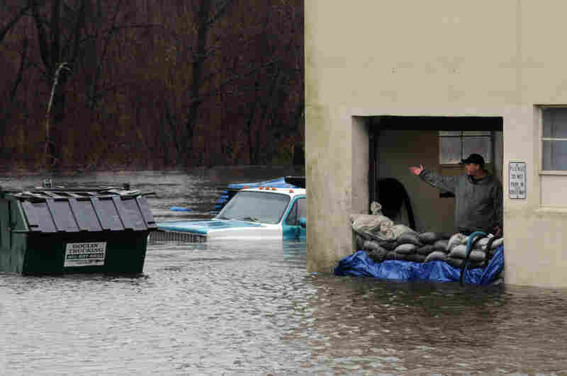 A man at Cycle King gestures to his flooded facility as the Pawtuxett River floods on Tuesday in Warwick, Rhode Island. National Guardmen were activated in Massachusetts and Rhode Island where a state of emergency was declared.