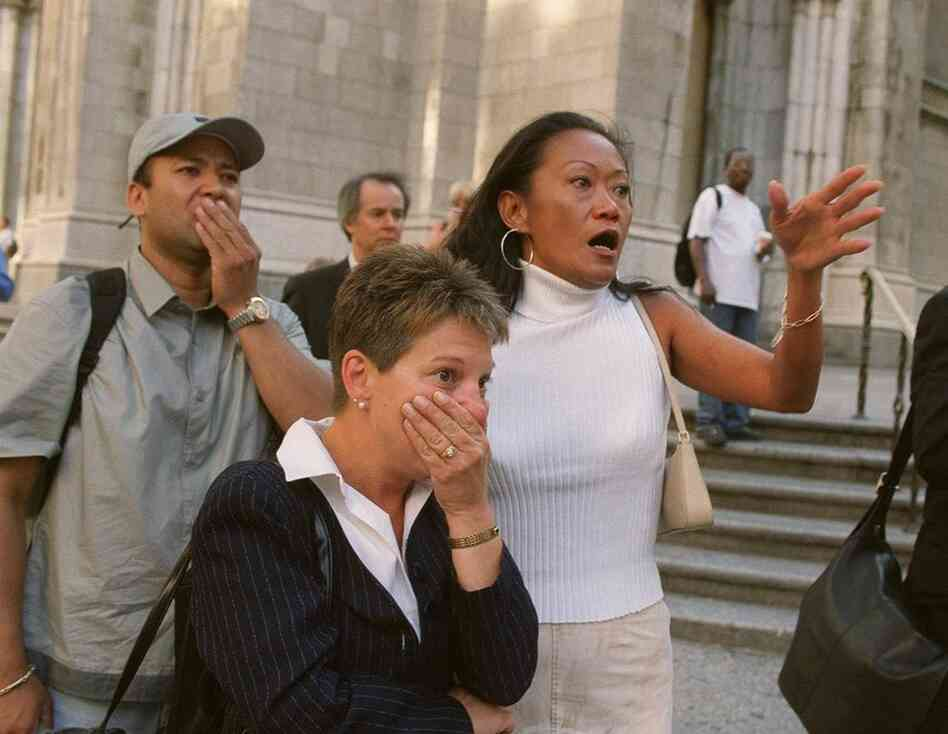 People in front of New York's St. Patrick's Cathedral react with horror as they see the World Trade Center towers after planes crashed into their upper floors.