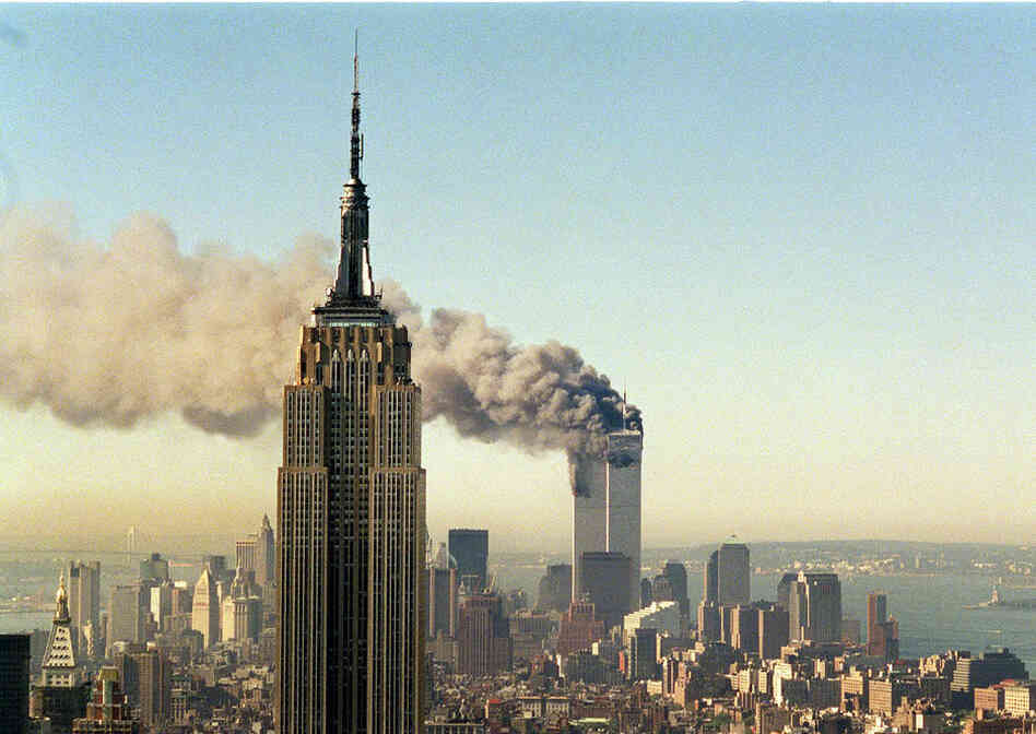 The twin towers of the World Trade Center burn behind the Empire State Building in New York, on Sept. 11, 2001.