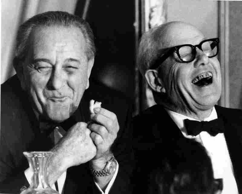 President Lyndon Johnson smiles while eating a cookie, while George Meany, president of the AFL-CIO, laughs at a speaker's remark during a Jewish labor committee dinner at the Sheraton in New York.