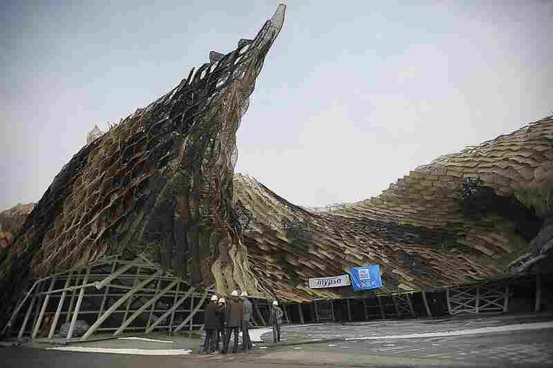 Workers gather at the Spain pavilion. The steel frame of the structure comprises 8,524 multicolored wicker panels.