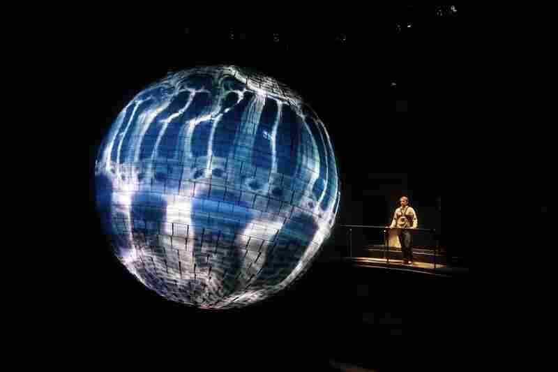"A performer at the Germany pavilion looks at the ""Energy Source,"" a 1.2-ton sphere with 400,000 LED lights that react to sound."