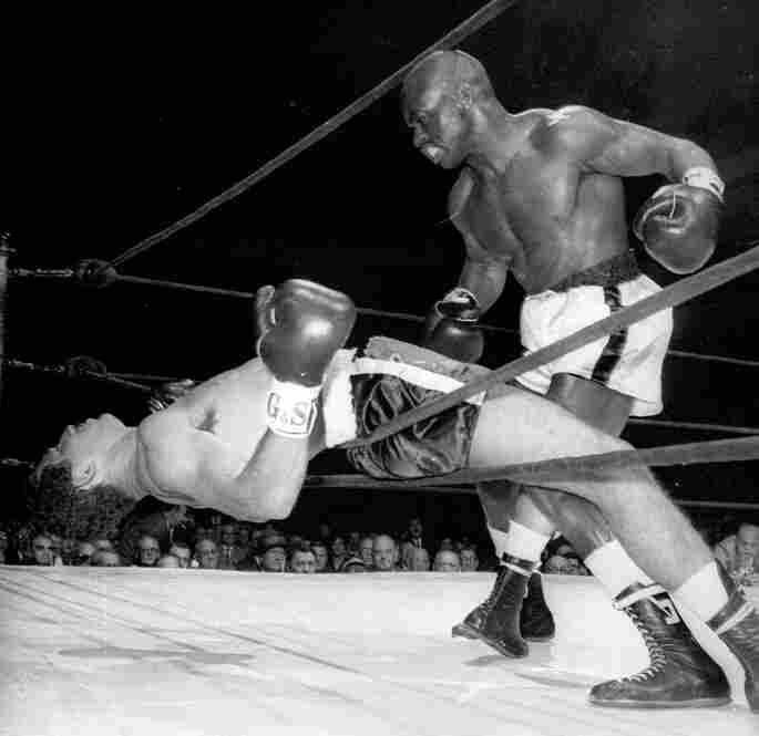 "Rubin ""Hurricane"" Carter of Paterson, N.J., watches Florentino Fernandez of Cuba fall through the ropes after being knocked out in the first round of a fight at New York's Madison Square Garden."