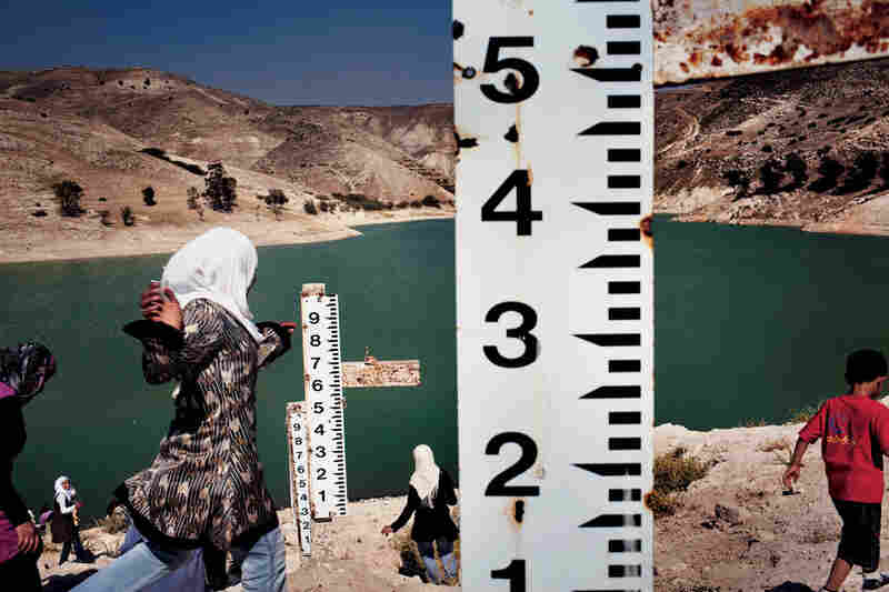 Measuring sticks, originally built to catch water flowing west into the Jordan River for irrigation, are useless at Jordan's Ziglad Dam. After six years of drought, this reservoir has shrunk to one-fifth of its capacity and hasn't filled since 2003, forcing Jordan to ration water.