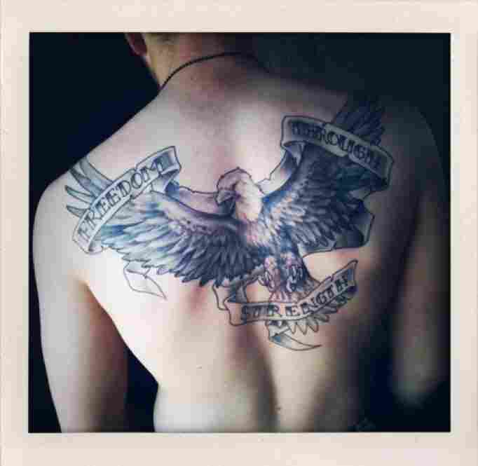 A tattoo covers the back of a U.S. Marine.