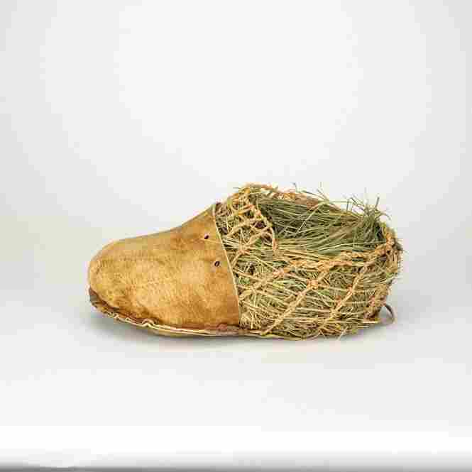 """This is a replica of footwear worn by the 5,300-year-old Neolithic man discovered in the Alps in 1991.  Grass """"socks"""" wicked away moisture and added comfort."""