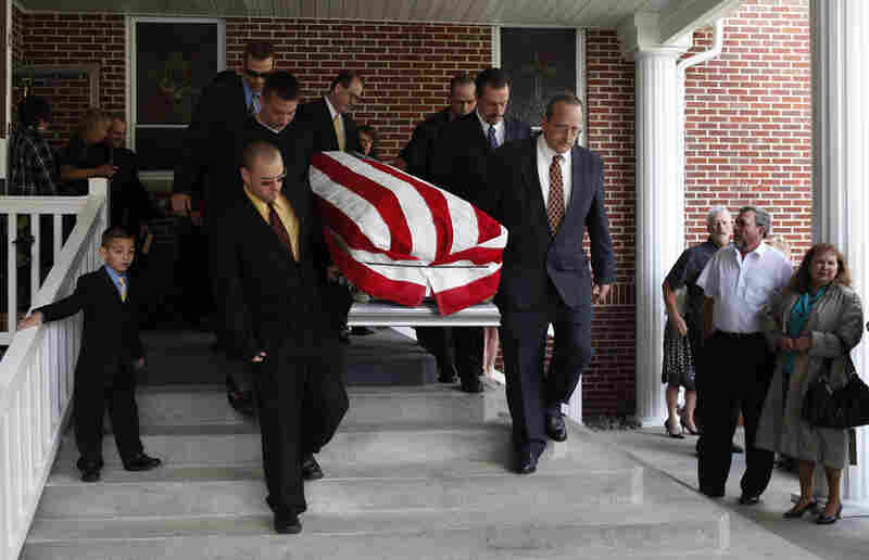 Pallbearers carry the flag-draped coffin of Benny Ray Willingham to a hearse after a funeral service.