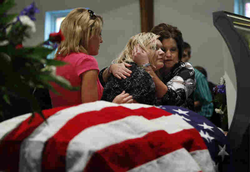 Tiffany Ellis (center) is comforted by Joy McGaha (right) and Jessica Cooper as they pause at the open, flag-draped coffin of Tiffany's grandfather Benny Ray Willingham during a funeral service at Mullens Pentecostal Holiness Church in Mullens, W.Va., on Friday. Willingham was among those killed in an explosion at Massey Energy Co.'s Upper Big Branch mine.