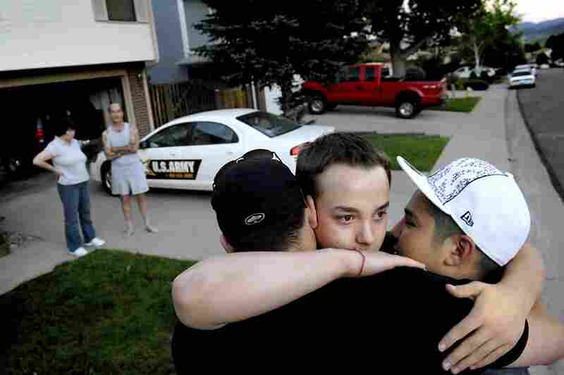 "June 17, 2007. 8:27 p.m. Ian embraces ""Buddha"" (left) and Shane as he prepares to leave home with Sgt. 1st Class Nancy Alessandri, who speaks to his dad in the driveway. Alessandri, an Army recruiter, took Ian to a hotel where he would spend the night before being bused to the Denver Military Entrance Processing Station."
