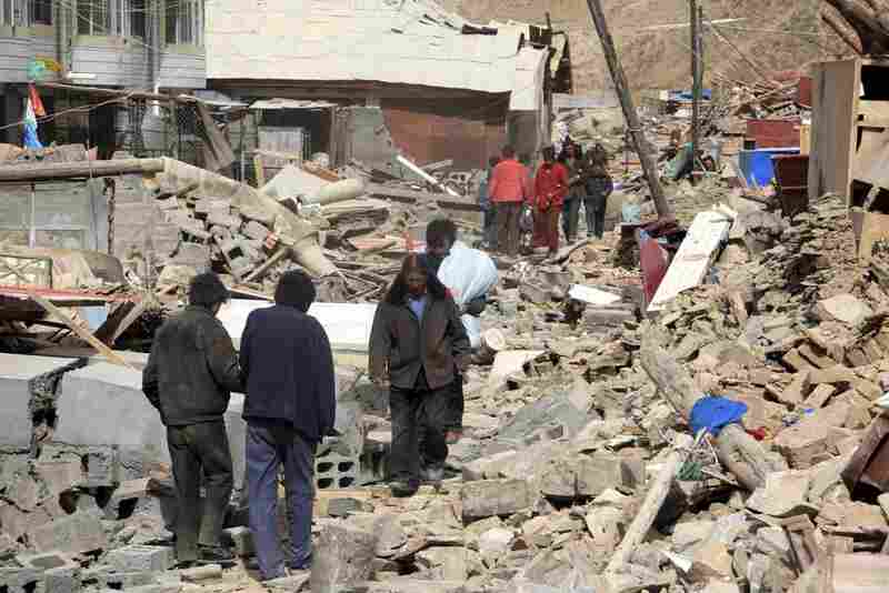 People walk on the ruins of crumbled buildings in Yushu. The earthquakes also triggered landslides, the official Xinhua news agency reported.