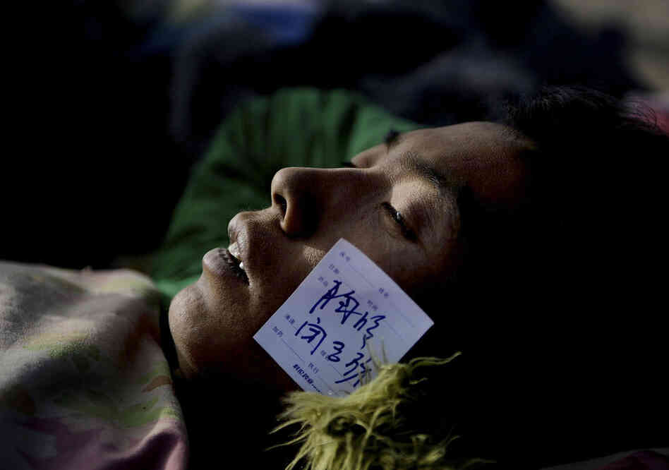 An injured survivor with a paramedic tag waits for medical treatment at a gymnasium following the earthquake in Yushu county in western China.
