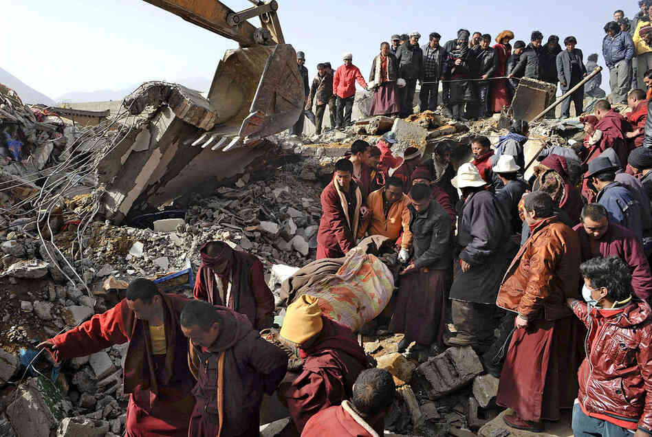 Rescue crews, including Buddhist monks, carry a blanket-wrapped earthquake victim pulled from the rubble Thursday after a magnitude 6.9 temblor hit Yushu county in China's Qinghai province. Rescue workers and equipment began streaming into the mountainous region a day after a series of quakes killed more than 600 people and injured thousands.