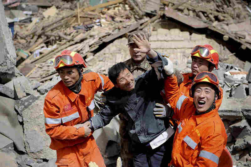 A survivor waves after being rescued from rubble of a collapsed building. The region sits at about 13,000 feet, and many rescue workers were suffering from altitude sickness.