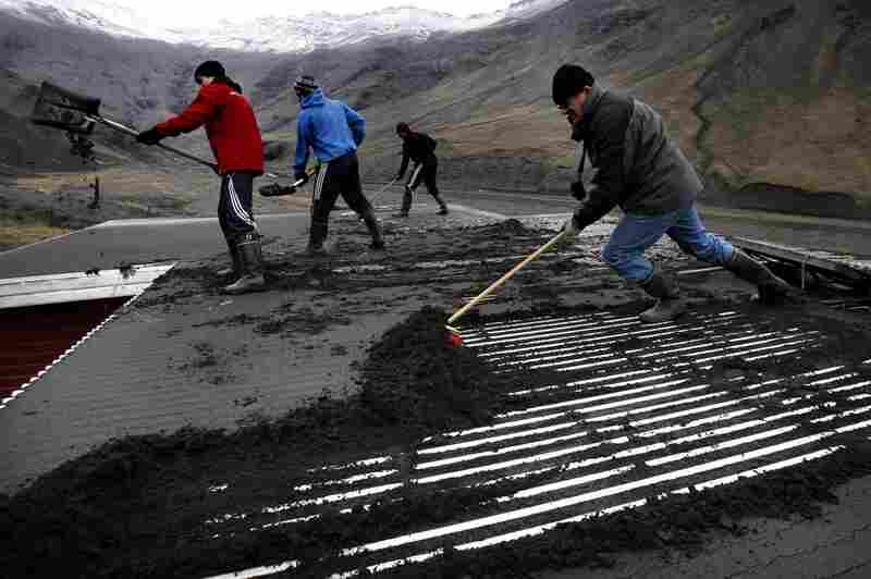 Men labor to remove volcanic ash from the roof of a house, in Seljavellir, Iceland,  April 18.