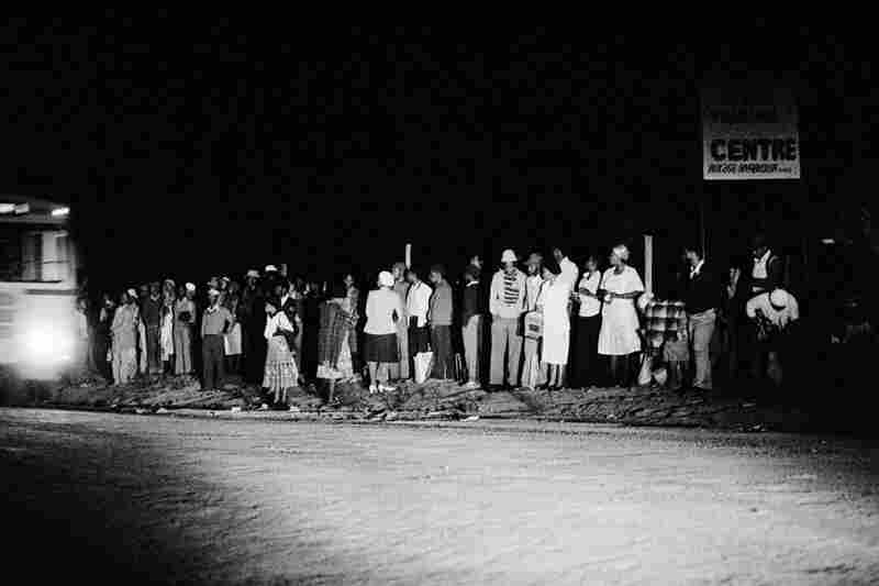 Going to work: workers in the KwaNdebele Bantustan queue at 2:40 a.m. for the first bus of the day to take them to their workplaces in Pretoria. The journey will take nearly three hours. Many will then take further transport of up to an hour in order to be at work by 7:00 a.m. There were (and are) very few employment opportunities in what was the KwaNdebele Bantustan. Mathysloop, February, 1...