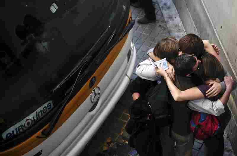 A family from Reading, England, embraces after getting bus tickets to France at the bus station in Barcelona, Spain, on April 19. The family had been stranded in Barcelona since April 15.