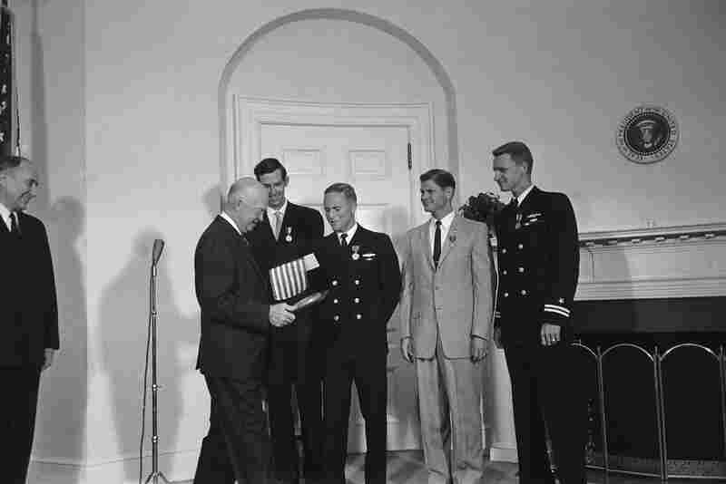 President Dwight Eisenhower looks at a plaque given to him by the crew of the Trieste and carries a small U.S. flag that was taken on the dive. At a White House ceremony, the president decorated four men for their work on the Trieste dive. From left to right: Piccard; Walsh; scientist Andreas B. Rechnitzer; and Navy Lt. Lawrence A. Shumaker. At left is Capt. E.P. Aurand, the president's naval a...