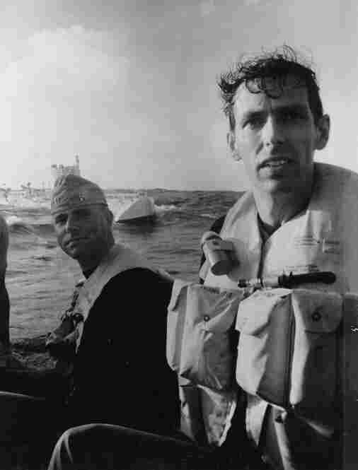 Spray-drenched and bone-tired, Walsh (left) and Piccard leave the Trieste in a rubber boat.