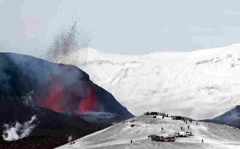 Tourists gather to watch lava spurt out of the Fimmvorduhals volcano, near the Eyjafjallajokull glacier.