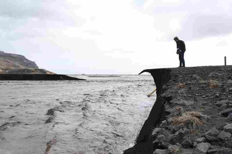 A man takes a picture of a road that has been washed away by floodwaters from the melting Eyjafjallajokull glacier, caused by the April 14 eruption.