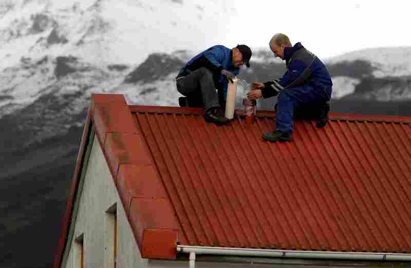 Men near Myrdalssandur, Iceland, wrap a house vent in plastic film on April 16 to prevent the entry of airborne volcanic ash. Winds pushed the ash plume south and east across Britain, Ireland, and Scandinavia into the heart of Europe.