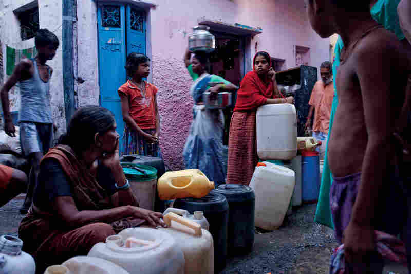 Slum dwellers in Delhi wait hours for water from a privately owned tap, but many will be turned away.