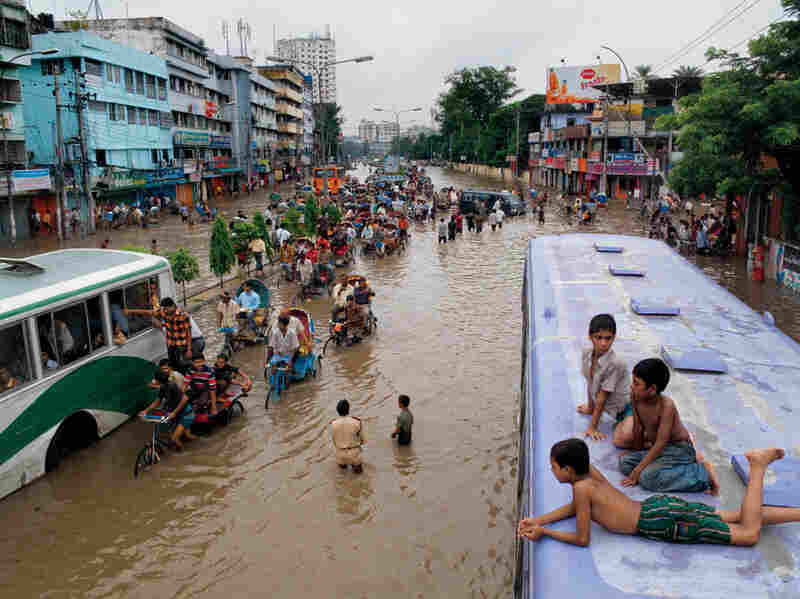 A stranded bus makes a dry perch in Dhaka, where Bangladeshis slog through the capital after a downpour turned the street into a river.