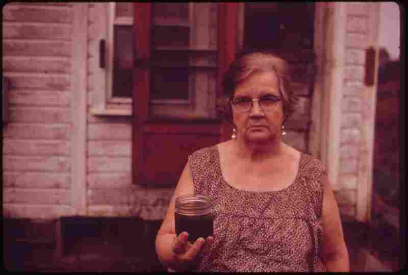 Mary Workman holds a jar of undrinkable water that comes from her well in Jefferson County, Ohio. She has filed a damage suit against the Hanna Coal Co. Although Hanna owns all the land around her, Workman refuses to sell. October 1973.