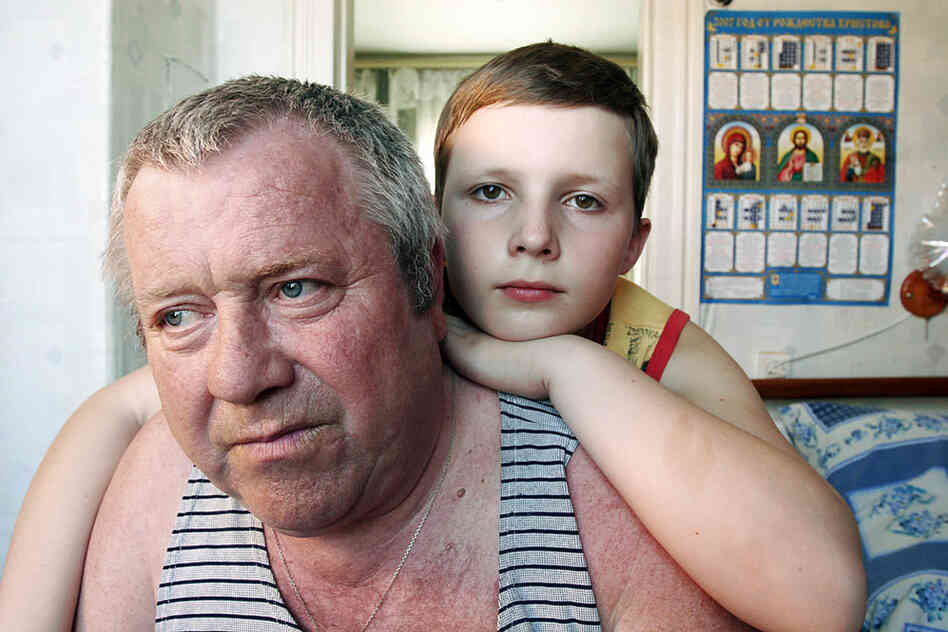 """""""In 1986, Leonid Budkovskiy (here with his grandson, Slava), then a mailman in Ivankiv, was reassigned to deliver top-secret mail to the military headquarters set up in Chernobyl. He continued for four years ... His legs slowly stopped working and by 1996 he was confined to a wheelchair."""""""