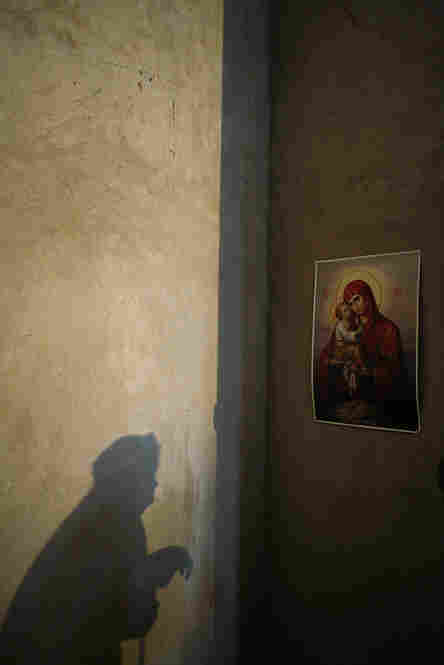 """""""An elderly woman prays before a poster of Mary and Jesus while Father Momotyuk Nazarii leads a service at the small Ukrainian church in Novo Ladizhichi village. The church has been under construction for a full decade, as villagers have had trouble raising enough money to continue building."""""""